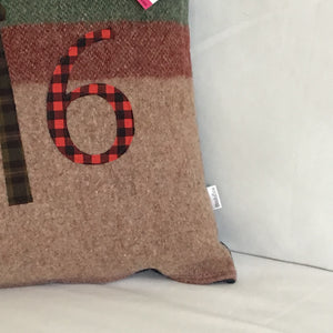 Light brown pillow with maroon and moss stripes with red plaid numbers and green check CN Tower.