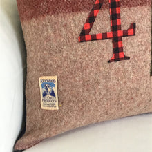 Load image into Gallery viewer, Light brown pillow with maroon and moss stripes with red plaid numbers and green check CN Tower.
