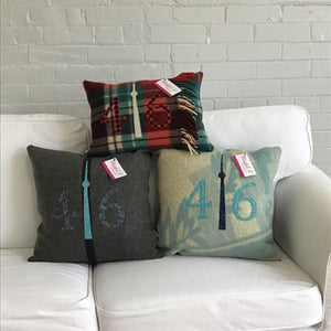 Dark grey pillow with modern black stripe.  Dark grey numbers and teal CN Tower.