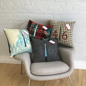 Cream pillow with chocolate brown squares. Red plaid numbers and green CN Tower.