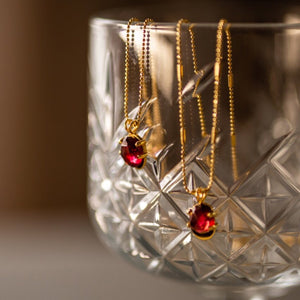 Garnet necklaces set in gold plated sterling silver, draped over crystal-cut whiskey glass