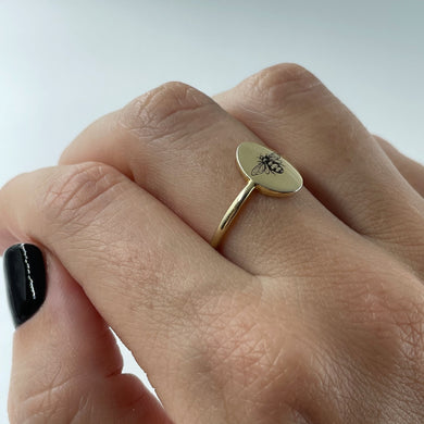 9ct gold oval ring with bee engraving, shown on hand