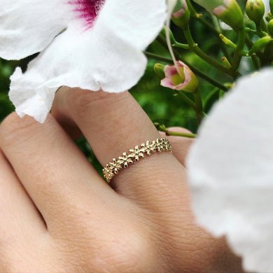 Solid gold ring with flower motif, shown on hand