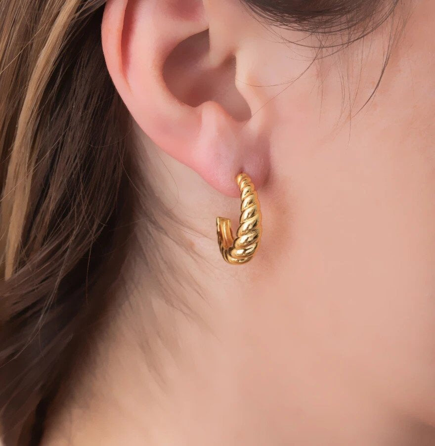 Golden rope twist hoop earring on ear