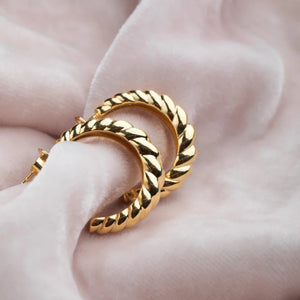Golden rope twist hoop earrings on velvet