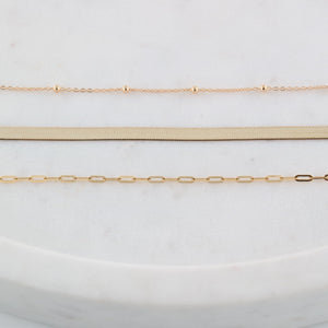 Three gold chains laid out in rows on marble
