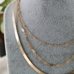 Three gold layering chains shown on grey bust