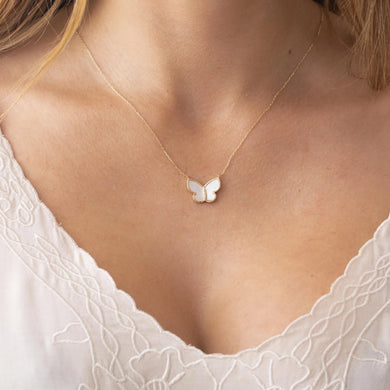 Solid gold, mother of pearl, diamond butterfly pendant on model's neck