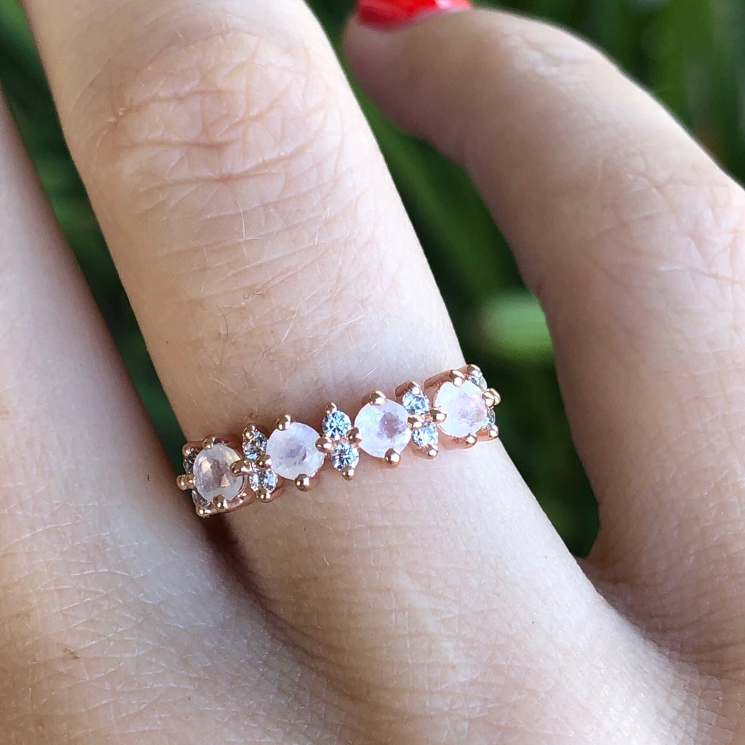 Rose gold ring band with natural rainbow moonstones and simulated diamonds, shown on hand