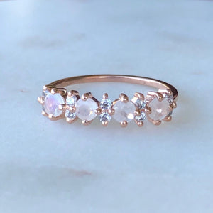 Rose gold band with simulated diamonds and rainbow moostones, shown on marble surface
