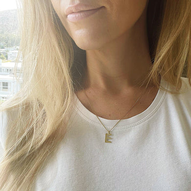 Collective & Co. Initial in solid gold on gold chain, shown on neck of blond woman in white t-shirt