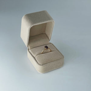 Nude coloured velvet ring box displayed open with La Kaiser Alexandrite Baguette ring inside