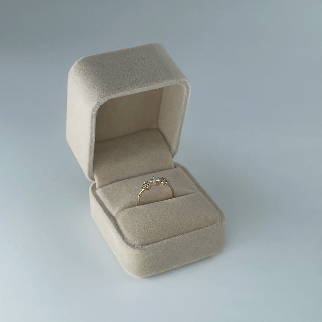 Velvet ring box in nude colour, displayed open with gold ring inside