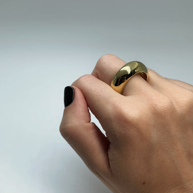 Extra thick brass ring shown on middle finger of female hand