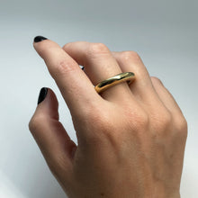 Load image into Gallery viewer, Thick brass ring on middle finger of female hand