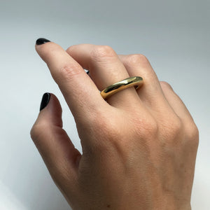 Thick brass ring on middle finger of female hand