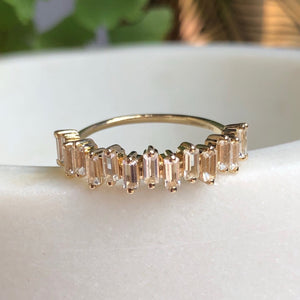 10kt Solid gold topaz bridge ring. Shown on marble surface