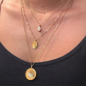 Layering necklaces made of solid gold, gemstones