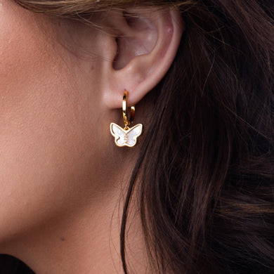 Gold and butterfly earring on ear