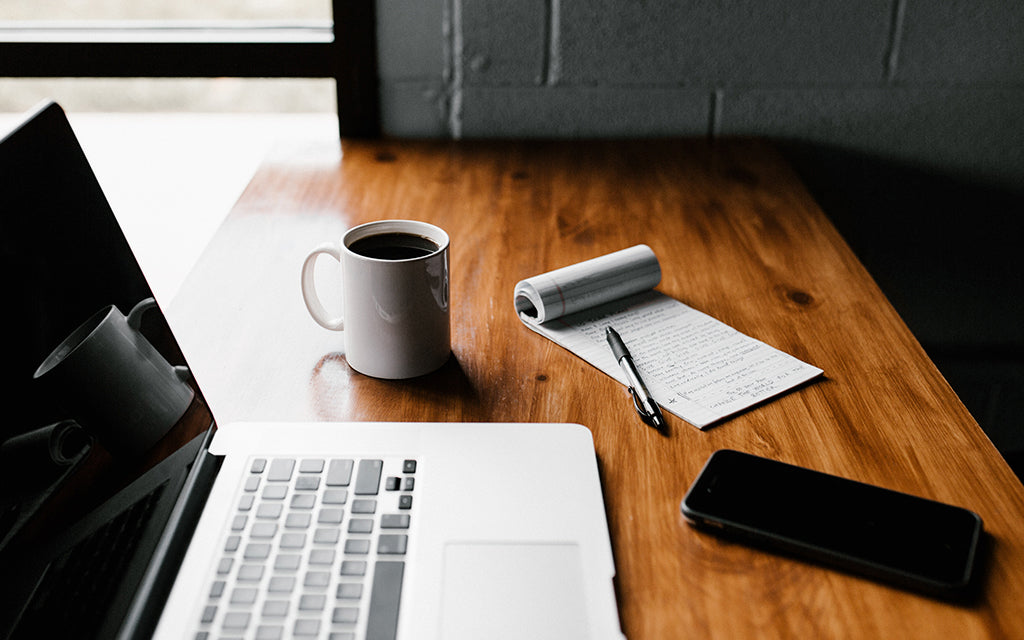 Computer, coffee cup and notebook
