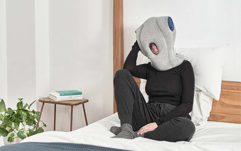 A person wearing Ostrichpillow Original Napping Pillow