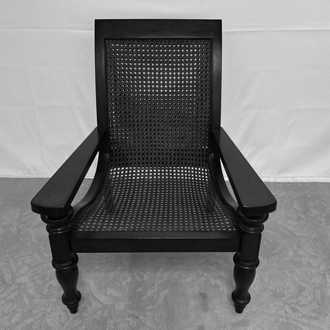 Elegantly masculine dark wood arm chair with well-turned front legs, caned back and seat