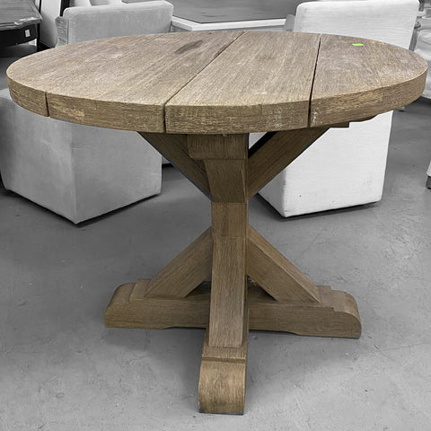 rough hewn planks form round tabletop on x-base dining table