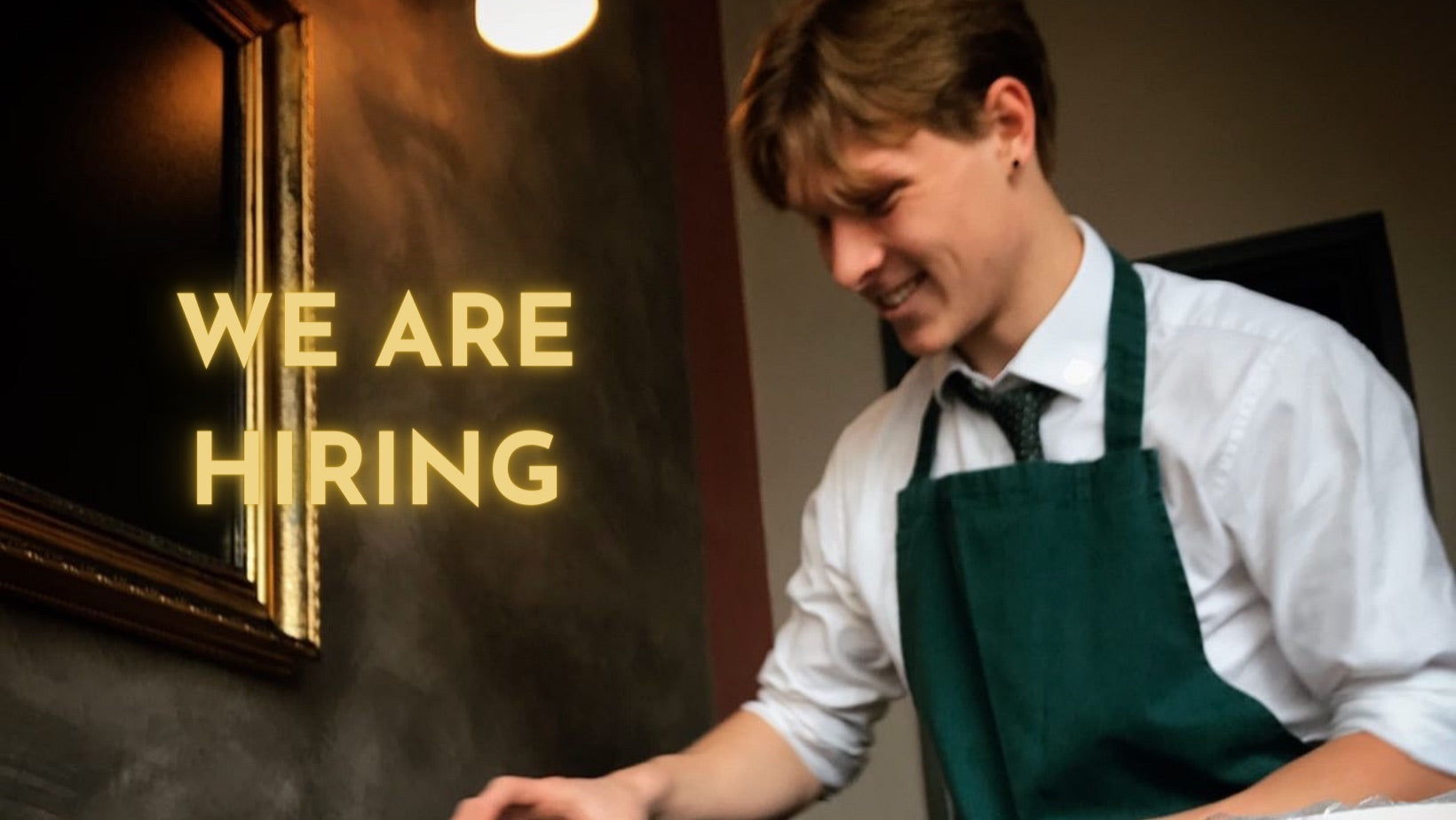 George smiling as he lays a table with the words WE ARE HIRING glowing in capital letters next to him