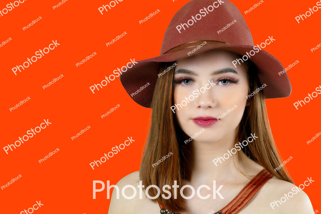 Model wearing brown hat on Red background