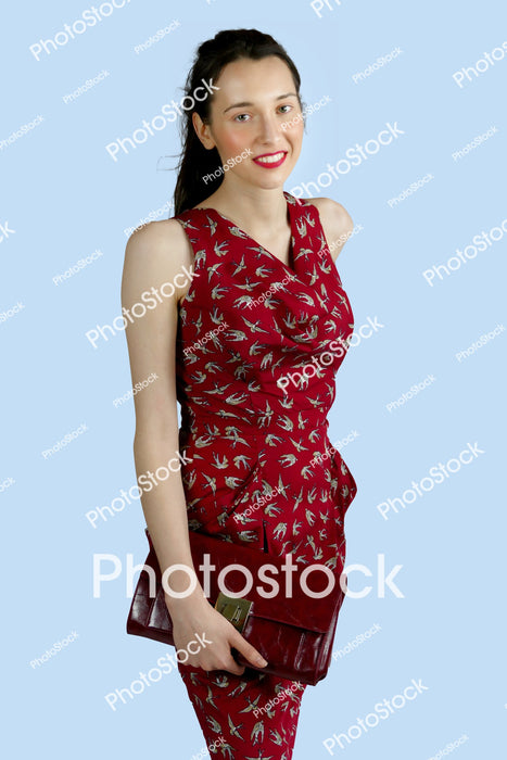 Young woman in red dress with red clutch bag