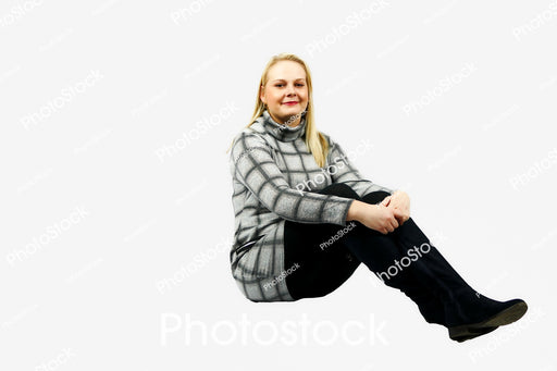 Woman sitting with legs out in grey checked top