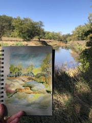 watercolor painting in foreground of landscape