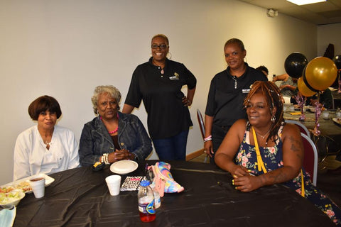 Shanta Lana Hereford and Tracy Dumas, back from left, were chatting with guests at a black town hall meeting on Sunday evening where those with Beloit Black Wall Street Inc. presented what the community-owned business plans to offer.  Hillary Gavan/Beloit Daily News