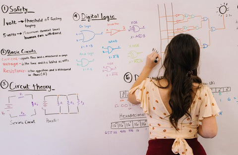 Woman drawing circuits on a whiteboard