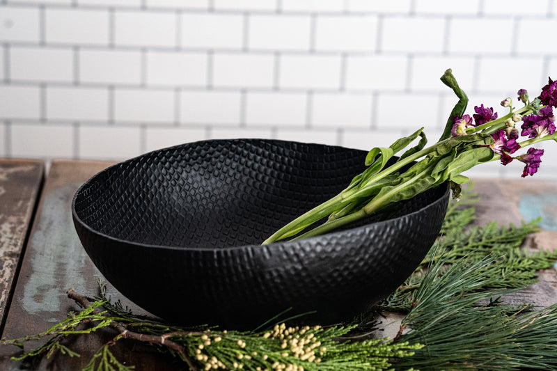 black crosshatch textured bowl with florals inside. subway tile wall in background reclaimed wood table top