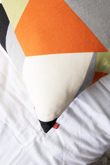 kravet geometric pattern: orange, black, white, gray, green. pillow on crisp white linen sheets