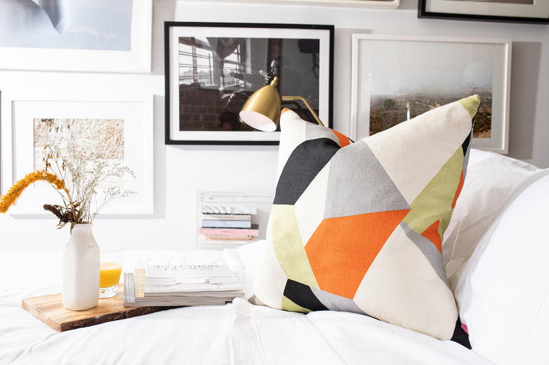 kravet geometric pattern: orange, black, white, gray, green. pillow on crisp white linen sheets with wood tray on top balancing white vase with florals and interior design magazines