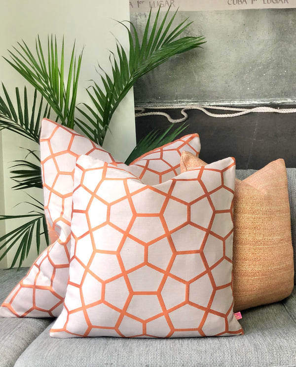 honeycomb orange pillows on grey sofa with large plant in corner against wall with oversized artwork