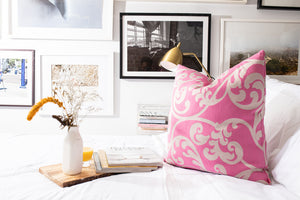 Damask pink and white throw pillow on crisp white bed linens. glass of orange juice, white milk vase with florals and stack of interior design magazine on wood tray.