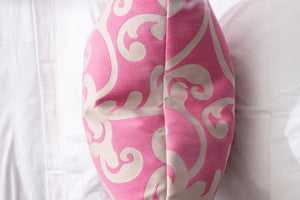 top of Damask pink and white throw pillow on crisp white bed linens.