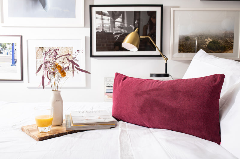 front  of Ribbed purple pillow cover with elan by uri signature pink invisible zipper on crisp white bed sheets next to interior design magazines on wood tray with glass of orange juice and white vase with flowers. gallery art wall with black and white frames and black and gold desk lamp