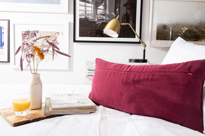 back of Ribbed purple pillow cover with elan by uri signature pink invisible zipper on crisp white bed sheets next to interior design magazines on wood tray with glass of orange juice and white vase with flowers. gallery art wall with black and white frames and black and gold desk lamp