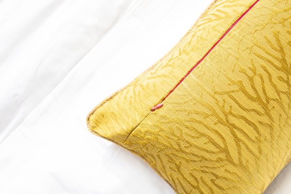 Citrine throw pillows with embroidered texture of vines throughout with gold piping on crisp white sheets with invisible pink zipper