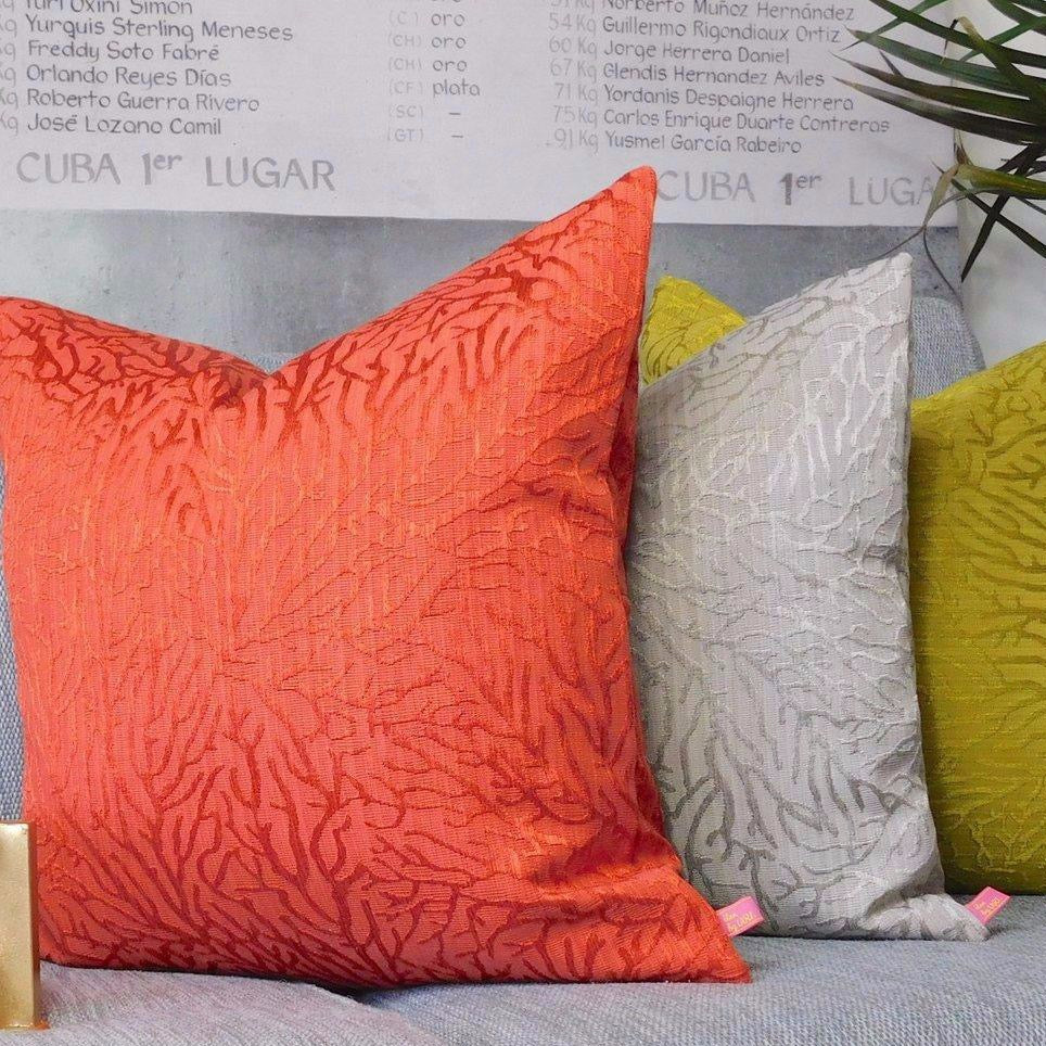three throw pillows in coral, silver and citrine with same fabric with vine detail and pink elan by uri tag.