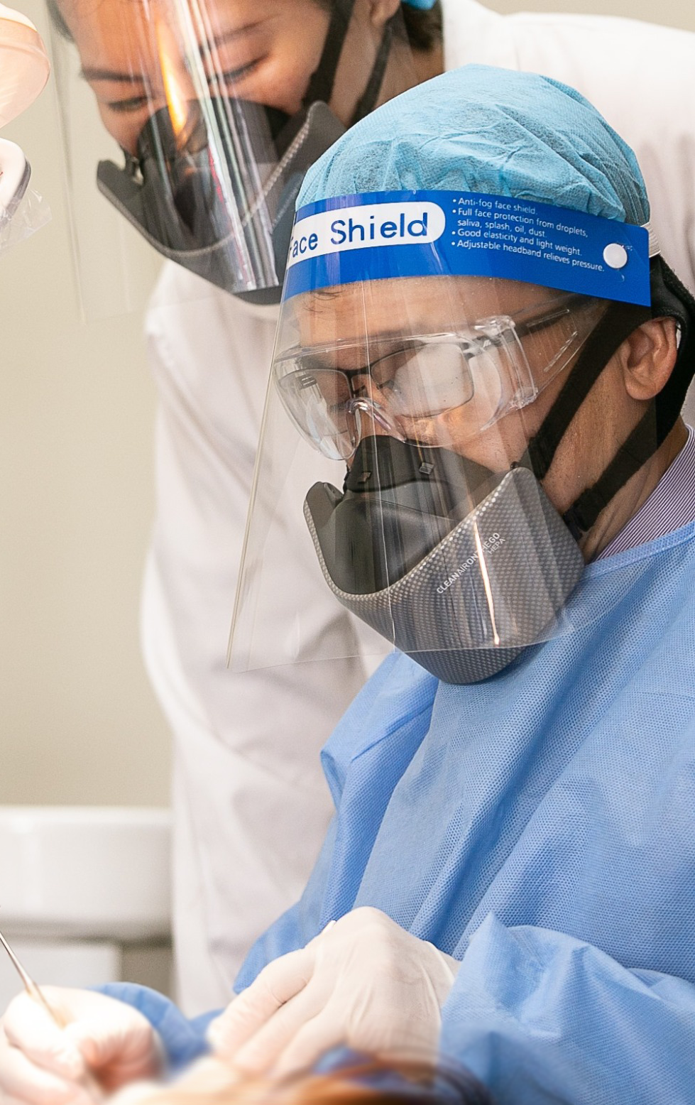 Surgeon and assistant performing a procedure with mask.