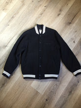 "Load image into Gallery viewer, Retreat wool varsity jacket in black with ""Canada"" printed on the chest,"