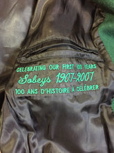 "Load image into Gallery viewer, Roots ""Sobey's Centenary Anniversary"" '07 varsity jacket in green and white with snap closures, slash pockets, knit trim, embroidered ""100"" emblem on the chest and ""07"" on the arm."