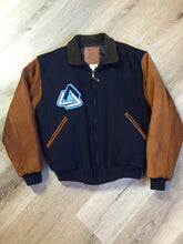 "Load image into Gallery viewer, Kingspier Vintage - AES 1997 brown and blue leather and wool varsity jacket with zipper, slash pockets , quilted lining, inside pocket, embroidered emblem on the chest and ""AES"" printed across the back."
