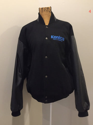 "Konica ""film and Cameras"" wool and leather varsity jacket in black with snap closures, slash pockets, inside pocket and ""get ready"" written across the back with a race car illustration. Size large."