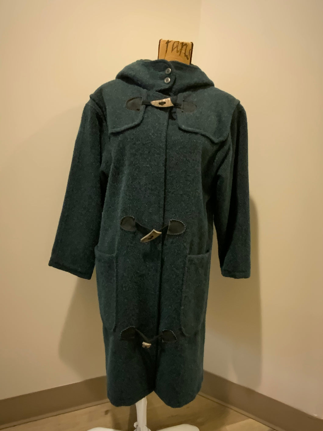 """The Woolrich Woman"" dark teal wool and mohair blend duffle coat with hood, pockets, three wooden toggles, inside snaps and a leather Woolrich label. Made in the USA. Fits a size small."